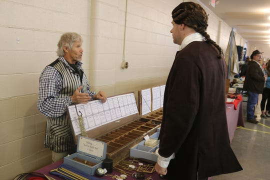 Scott and Renee Rathfelder, of Smiling Fox Forge in Fremont, speaks with a reenactor at the Living History Trade Fair on Saturday.