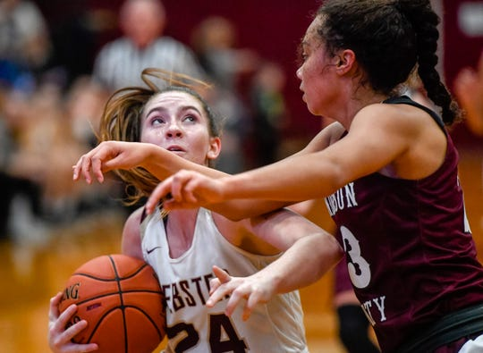 Webster County's Adeline McDyer (24) looks to shoot over Henderson County's Jocelyn Spaulding (23) as district rivals the Henderson County Lady Colonels play the Webster County Lady Trojans in Dixon Friday evening, January 31, 2020.