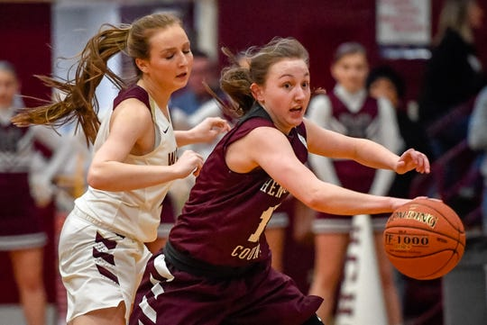 Henderson County's Sadie Wurth (15) picks up a loose ball from Webster County's Marissa Austin (2) as district rivals the Henderson County Lady Colonels play the Webster County Lady Trojans in Dixon Friday evening, January 31, 2020.