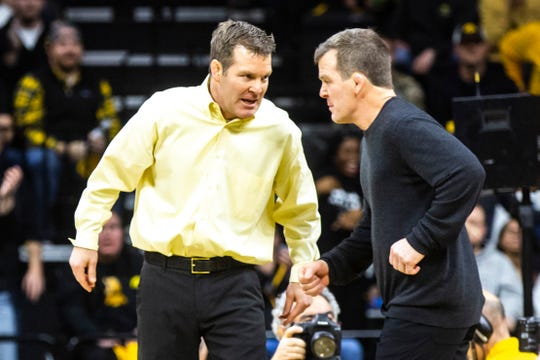 Iowa head coach Tom Brands, left, talks with associate head coach Terry Brands during a NCAA Big Ten Conference wrestling dual against Penn State, Friday, Jan. 31, 2020, at Carver-Hawkeye Arena in Iowa City, Iowa.