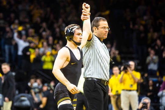 Iowa's Spencer Lee has his hand raised after winning a match at 125 pounds during a NCAA Big Ten Conference wrestling dual against Penn State, Friday, Jan. 31, 2020, at Carver-Hawkeye Arena in Iowa City, Iowa.