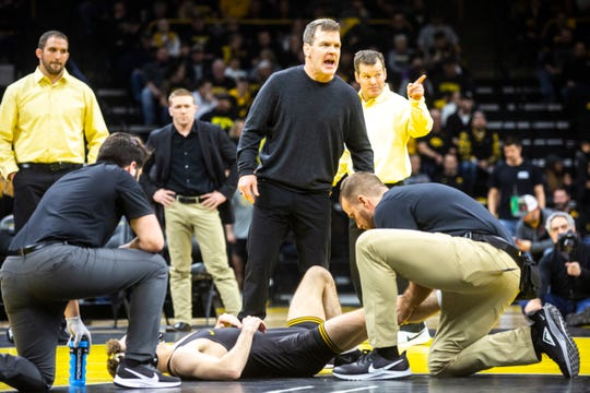 Iowa associate head coach Terry Brands calls out to an official while trainers check on Austin DeSanto during his match at 133 pounds during a NCAA Big Ten Conference wrestling dual, Friday, Jan. 31, 2020, at Carver-Hawkeye Arena in Iowa City, Iowa.