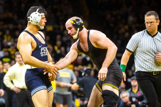 Iowa's Alex Marinelli, center, shakes hands with Penn State's Vincenzo Joseph after losing the match at 165 pounds during a NCAA Big Ten Conference wrestling dual, Friday, Jan. 31, 2020, at Carver-Hawkeye Arena in Iowa City, Iowa.