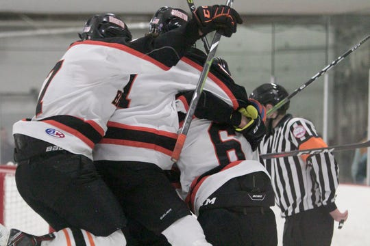 Brighton teammates congratulate Brady MacDonald (6) on his tying goal with 1.2 seconds left in the third period of a 3-3 tie with Hartland on Friday, Jan. 31, 2020 at the Kensington Valley Ice House.