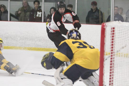 Brighton's Brady MacDonald (6) scores one of his three goals against Hartland goalie Ryan Piros during a 3-3 tie on Friday, Jan. 31, 2020.