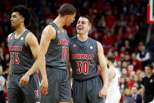 Ryan McMahon (30) celebrates a 3-pointer with Samuell Williamson (10) during Louisville's win at NC State.