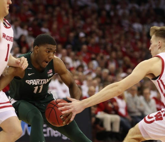 Michigan State Spartans forward Aaron Henry (11) tries to keep ball from Wisconsin Badgers forward Tyler Wahl (right) during the firsts half at the Kohl Center.