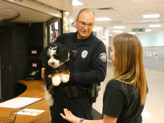 Marion Police Officer Dave Dunaway, center, a school resource officer, holds Chip, the police department's emotional support K9 Friday as Grant Middle School students, including Ava Esterline, 12, right, pause to pet him. The police department hopes to extend its youth outreach to help at-risk youth avoid a criminal record.
