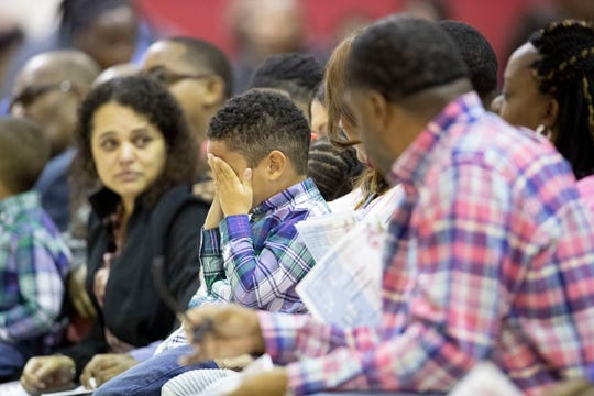 A young boy wipes his eyes during the funeral service Saturday.