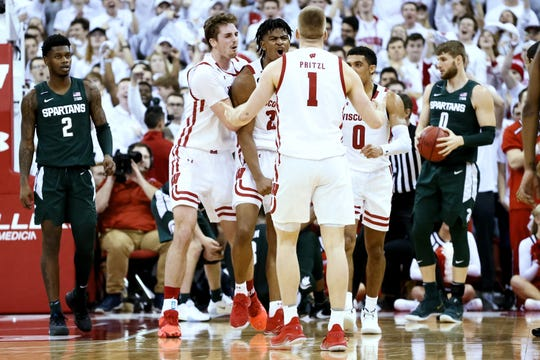 Aleem Ford celebrates with teammates Nate Reuvers, left, and Brevin Pritzl during the second half of Wisconsin's upset victory over Michigan State.
