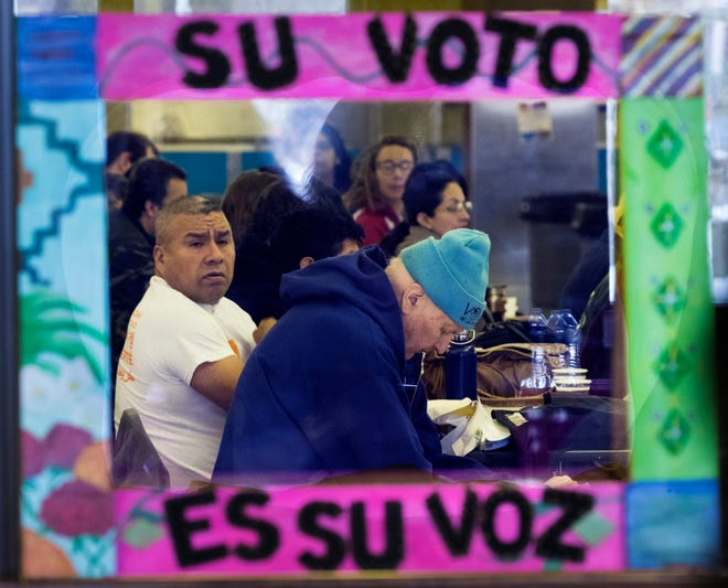 """Framed by the words """"Your vote is your voice"""" in Spanish, people listen to Democratic officials and candidates at a get-out-the-vote event in Milwaukee sponsored by immigrant advocacy group Voces de la Frontera on Saturday."""
