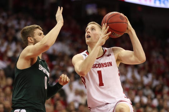 Badgers guard Brevin Pritzl goes up for a basket as Michigan State guard Kyle Ahrens defends.