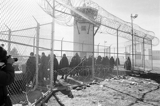 In this Feb. 5, 1980 file photo Prison inmates, wrapped in blankets, are pictured between the border fencing at the New Mexico State Penitentiary in Santa Fe, New Mexico, where they were guarded after the prison was destroyed during weekend rioting. Forty years after inmates seized control of the New Mexico State Penitentiary, the costs related to the uprising are still being tallied.
