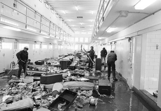 In this Feb. 4, 1980 file photo Guards at the New Mexico State Penitentiary work to clean up cell block six at the prison in Santa Fe, New Mexico. Forty years after inmates seized control of the New Mexico State Penitentiary, the costs related to the uprising are still being tallied.