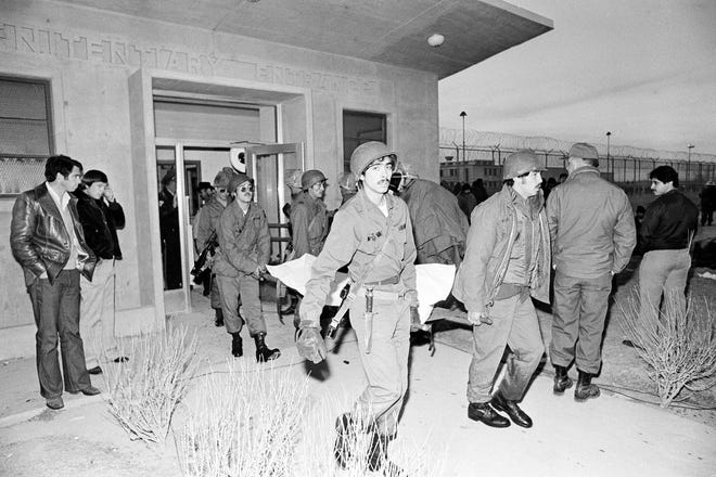 In this Feb. 3, 1980 file photo National Guardsmen carry the body of a prison inmate from the main entrance to the New Mexico State Penitentiary in Santa Fe, New Mexico. Forty years after inmates seized control of the New Mexico State Penitentiary, the costs related to the uprising are still being tallied.