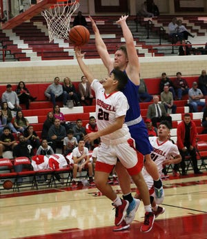Roswell's Dayton Gonzales goes for a fastbreak layup as Carlsbad's Ayden Parent goes for a block in Friday's district game. Roswell won, 62-49.