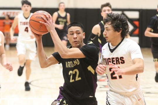 Kirtland Central's Cameron Crawford drives toward the basket for a layup against Aztec's Javier Valenzuela during Friday's District 1-4A boys basketball game at Lillywhite Gym in Aztec.