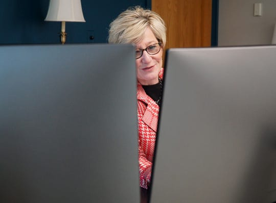 Livonia Mayor Maureen Brosnan at her City Hall desk - behind her two computer monitors. The mayor says that one of the monitors is simply for reading and writing emails and the other is for the rest of her business as the city's leader.