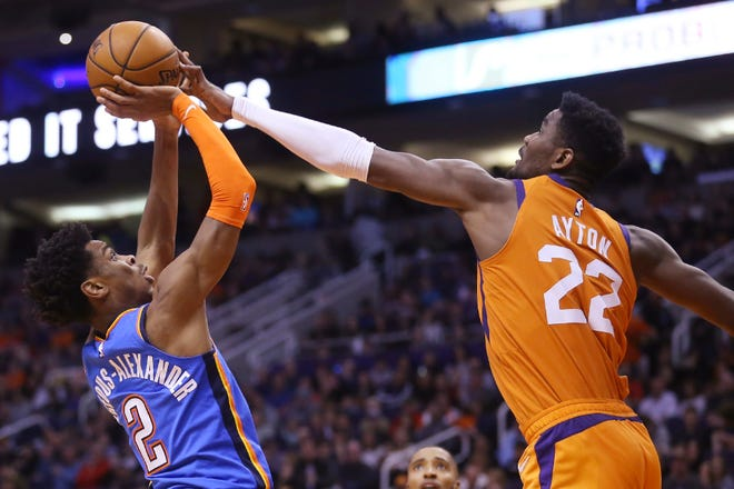 Phoenix Suns center Deandre Ayton (22) blocks the shot of Oklahoma City Thunder guard Shai Gilgeous-Alexander (2) during the first half of an NBA basketball game Friday, Jan. 31, 2020, in Phoenix. (AP Photo/Ross D. Franklin)
