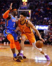 Suns' Devin Booker (1) drives against Thunder's Luguentz Dort (5) during the first half at the Talking Stick Resort Arena in Phoenix, Ariz. on January 31, 2020.