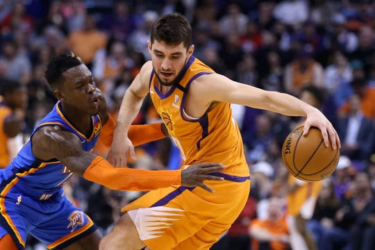 Oklahoma City Thunder guard Dennis Schroeder, left, reaches in to attempt a steal from Phoenix Suns guard Ty Jerome during the first half of an NBA basketball game Friday, Jan. 31, 2020, in Phoenix. (AP Photo/Ross D. Franklin)
