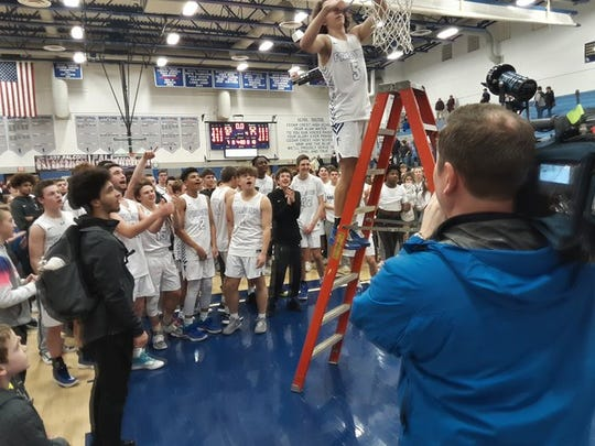 Cedar Crest's Chris Danz cuts down a portion of the net as his teammates await their turn amid the celebration of the Falcons' Section 1 title-clinching win over McCaskey Friday night.