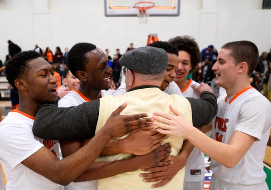 York High players hug assistant coach Dave Graybill after winning the YAIAA boys' basketball championship over Central York in 2015. Graybill was a fixture at York High events for half a century.