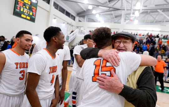 William Penn's Trey Shifflett hugs assistant coach Dave Graybill after winning the YAIAA boys' basketball championship over Central York in 2015.