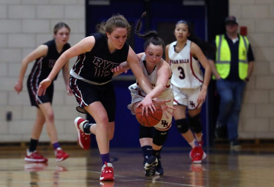From left, Rye's Teaghan Flaherty (12) and Byram Hills' Olivia Picca (23) battle for a loose ball during girls basketball action at Byram Hills High School in Armonk  Jan. 31, 2020. Rye won the game 62-54.