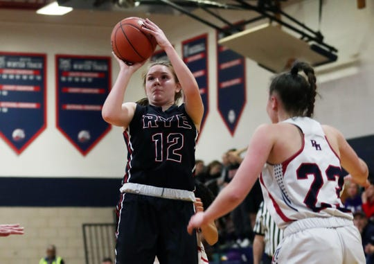 From left, Rye's Teaghan Flaherty (12) puts up a shot in front of Byram Hills' Olivia Picca (23) during girls basketball action at Byram Hills High School in Armonk  Jan. 31, 2020. Rye won the game 62-54.