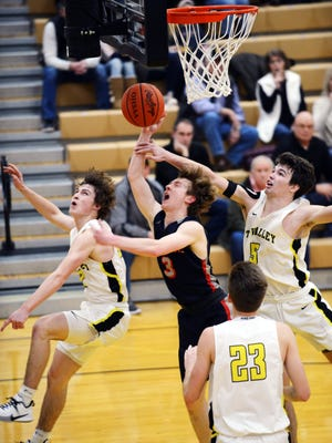 Morgan's Josh Wells has his shot challenged by Tri-Valley's Skye Bryan, left, and Keaton Williams on Friday night in Dresden. The Scotties won, 64-57, to stay within one game of the Muskingum Valley League lead.