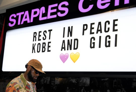 Lakers star LeBron James passes a sign to honor Kobe and Gigi Bryant at Staples Center as he arrives for the game against the Portland Trail Blazers on Jan. 31.