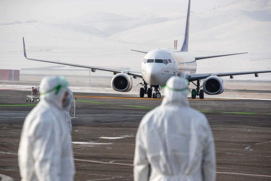 Staff members, wearing protective suits, watch as a plane carrying 32 Mongolian citizens for their evacuation from the Chinese city of Wuhan arrives in Ulaanbaatar, the capital of Mongolia on February 1, 2020. China faced deepening isolation over its coronavirus epidemic on February 1 as the death toll soared to 259, with the United States leading a growing list of nations to impose extraordinary Chinese travel bans.