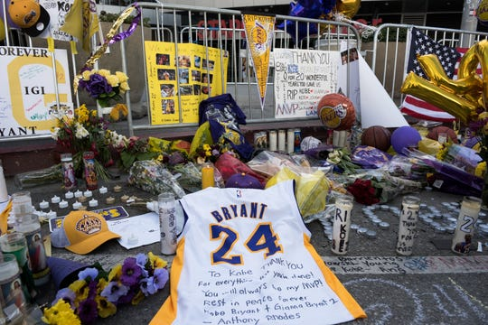 Fans leave momentos, including a Kobe Bryant jersey, at a makeshift memoral outside of Staples Center as the Lakers hosted the Portland Trail Blazers in their first game after Bryant's death.