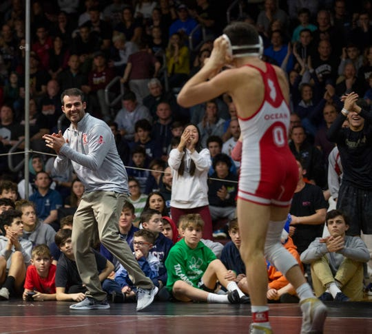 Ocean's Jack Nies (right) after he recorded the winning takedown in his 6-4 overtime win over Toms River East's Michael Conklin in the 132-pound championship bout of the Shore Conference Tournament. Ocean coach Cip Apicelli is applauding on the right.