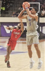 ACU's Payten Ricks, right, shoots a 3-point goal as Incarnate Word's Dwight Murray defends in the second half. ACU beat the Cardinals 72-58 in the Southland Conference game Saturday, Feb. 1, 2020, at Moody Coliseum.
