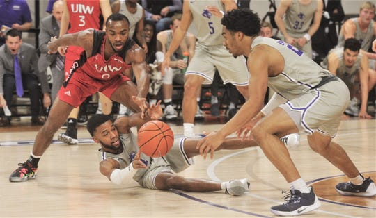 ACU's Reggie Miller, center, passes the ball to Coryon Mason after coming up with a loose ball as Incarnate Word's Dwight Murray defends in the second half. ACU beat the Cardinals 72-58 in the Southland Conference game Saturday, Feb. 1, 2020, at Moody Coliseum.