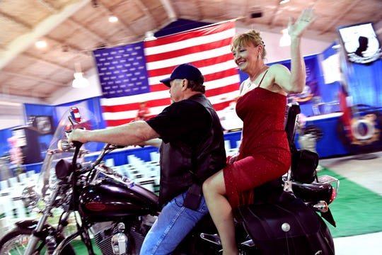 Amber Harris rides up to the stage with her husband Billy, to lip-synch a Reba McEntire song during the USO show Saturday.