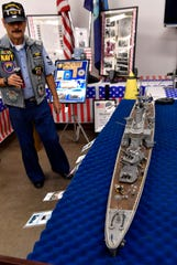 Luis Gonzalez, who served on the USS Newport News (CA-148) from 1970-74, stands beside his homemade model of his ship. His display tells the story of the heavy cruiser and the 19 men who lost their lives in a firing mishap with one of the ship's 8-inch guns.