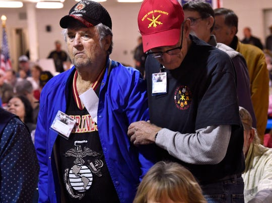 "U.S. Army veteran Danny McGowen (right) assists U.S. Marine Corps veteran Rick Zabel to stand as the ""Marine Hymn"" is played during the Armed Forces Medley at Saturday's TET Reunion at the Taylor County Expo Center."