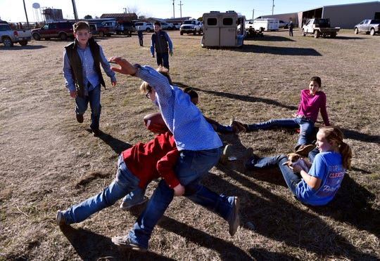 Fifth-grader Colter Edgar gets tackled by third-grader Slayton Parsons as a group of boys played football after showing their pigs during the 2020 Shackelford County Youth and Livestock Show in Albany on Jan. 24. Below, sixth-grader Jayden Kelly leans back to protect the puppy with which she and seventh-graders Averie Burns (right) and Jalea Bowman were playing.