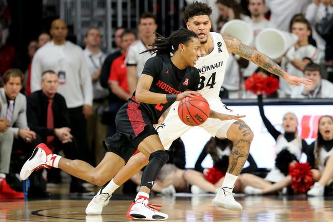 Houston Cougars guard Caleb Mills (2) drives to the basket as Cincinnati Bearcats guard Jarron Cumberland (34) defends in the second half during a college basketball game, Saturday, Feb. 1, 2020, at Fifth Third Arena in Cincinnati. Cincinnati Bearcats won 64-62.