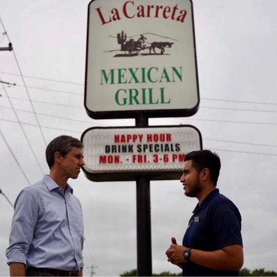 "Former Democratic presidential hopeful Beto O'Rourke speaks to Alfonso Medina, a Latino business owner at ""La Carreta Mexican Grill,"" which has become a common stop for candidates hoping to reach out to Latino voters in the state."