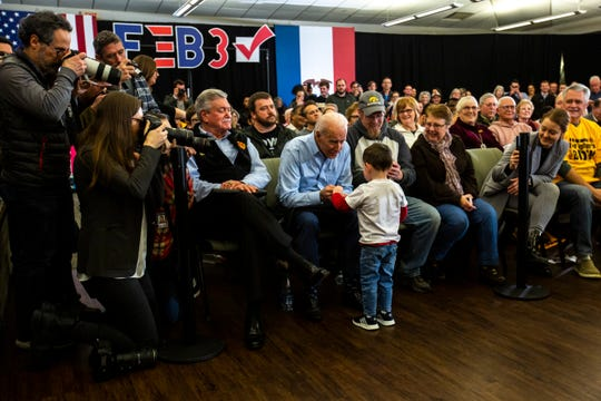 Former Vice President Joe Biden gives Burck Washburn, 3, of Iowa City, a challenge coin after speaking during a campaign event on Saturday at the South Slope Community Center in North Liberty.