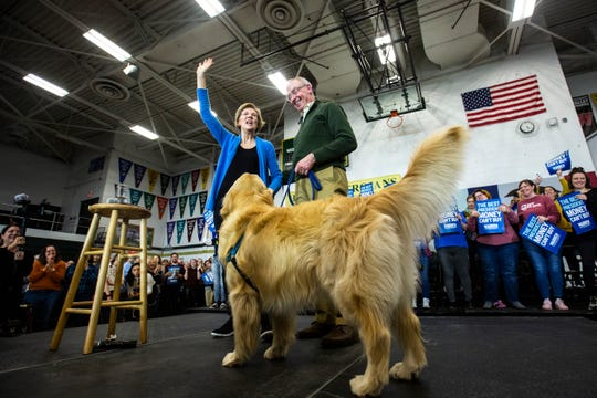 Democratic presidential candidate U.S. Sen. Elizabeth Warren of Massachusetts is joined by her husband, Bruce Mann, and their dog, Bailey, after speaking Saturday at West High School in Iowa City.