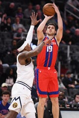 Detroit Pistons guard Sviatoslav Mykhailiuk shoots as Denver Nuggets forward Torrey Craig defends at Little Caesars Arena, Feb. 2, 2020.