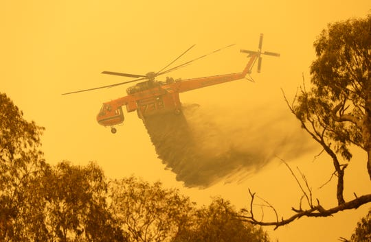 A helicopter drops water on a fire near Bumbalong, south of the Australian capital, Canberra, Saturday, Feb. 1, 2020.