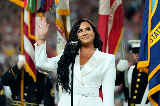Demi Lovato waves after performing the national anthem before the NFL Super Bowl 54 football game between the San Francisco 49ers and the Kansas City Chiefs Sunday, Feb. 2, 2020, in Miami Gardens, Fla.