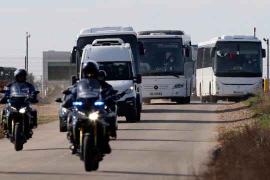 French passengers in buses leave a military air base, Friday Jan.31, 2020 in Istres, southern France.