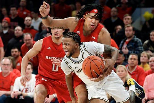 Michigan's Zavier Simpson (3) drives past Rutgers's Daniel Lobach (2) during the second half.